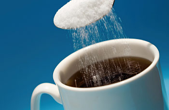 artificial-sweeteners being put in a coffee cup-350